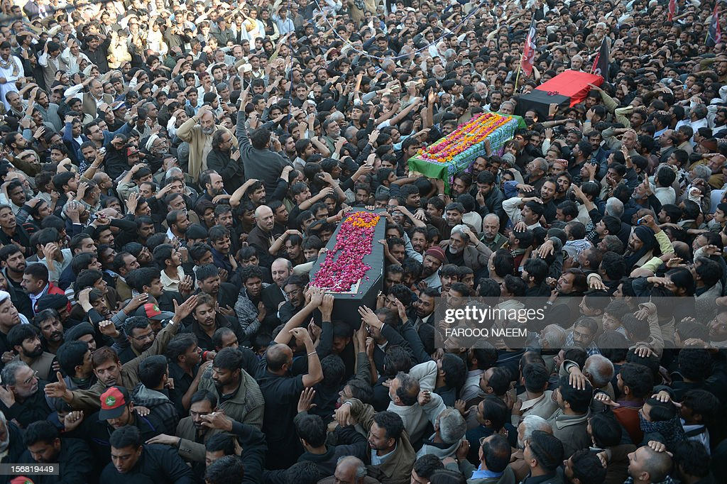 Pakistani Shiite and Sunni Muslims gather as coffins of bomb blast victims arrive for funeral prayers in Rawalpindi on November 22, 2012. Muslim leaders gathered for a rare summit in Islamabad on Thursday as militant attacks killed 36 people across the country on one of the deadliest days of violence claimed by the Taliban in months. AFP PHOTO/Farooq NAEEM