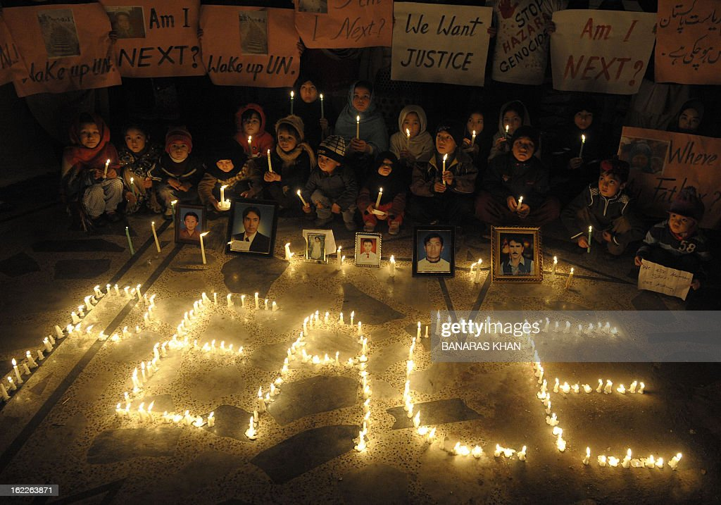 Pakistani Shiite Muslim children hold candles on February 21, 2013 near photos of victims during a vigil at the site of a bomb attack in Quetta. 89 people were killed when a massive bomb tore through a market in the Quetta suburb of Hazara Town on February 16, 2013. AFP PHOTO / Banaras KHAN