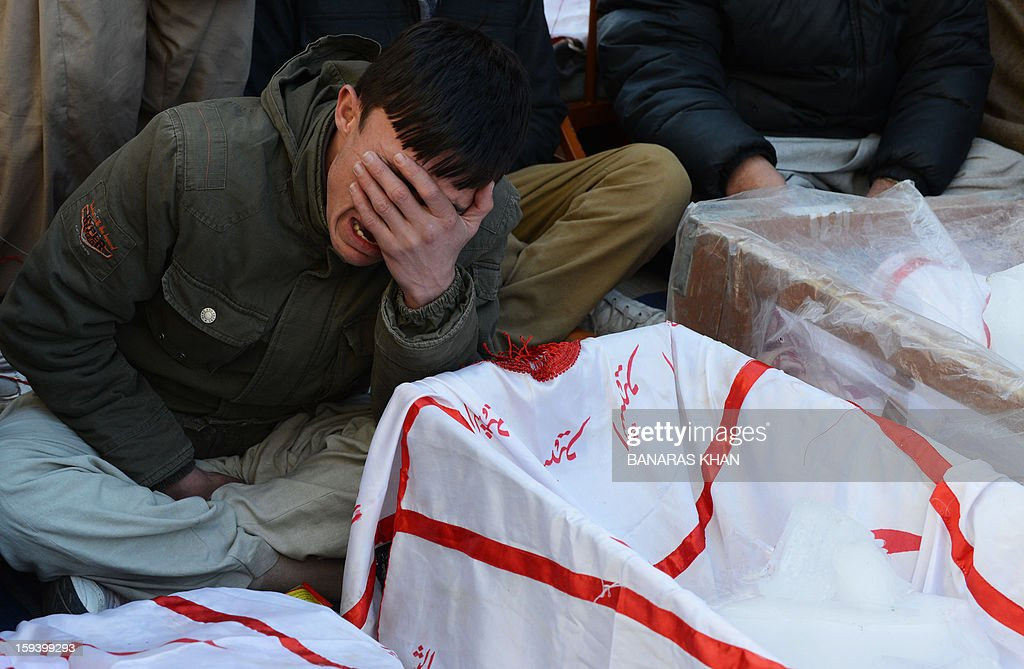 A Pakistani Shiite Muslim cries as he sits along with coffins of bomb blast victims in Quetta on January 13, 2013, on the third day of protest. Pakistan's Prime Minister Raja Pervez Ashraf arrived, in the southwestern city of Quetta to meet Shiite Muslim families refusing to bury their dead after devastating bombings. AFP PHOTO/ Banaras KHAN