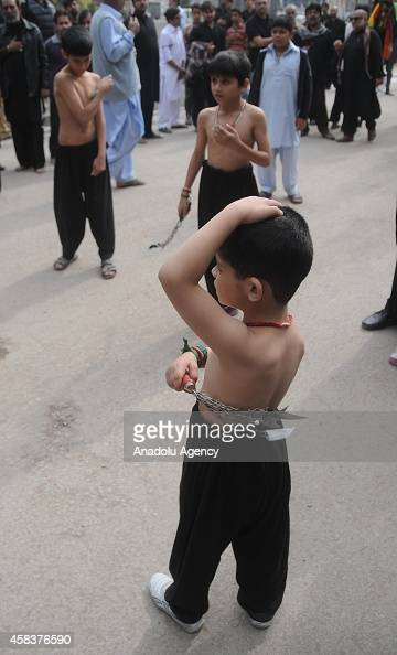 Pakistani Shiite Muslim devotee boys flagellate themselves with knifefitted chains during the mourning procession of Ashura on the 10th day of holy...