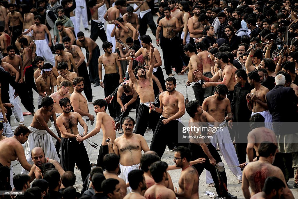 Pakistani Shiite Muslim devotee men flagellate themselves with chains during the mourning procession of Ashura on the 10th day of holy month of...