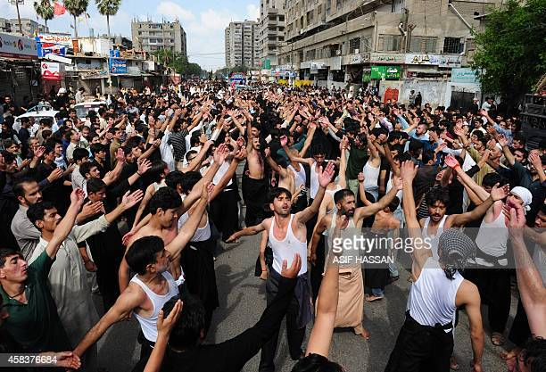 Pakistani Shiite Muslim devotees beat their chests during a religious procession marking Ashura in Karachi on November 4 2014 Ashura mourns the death...