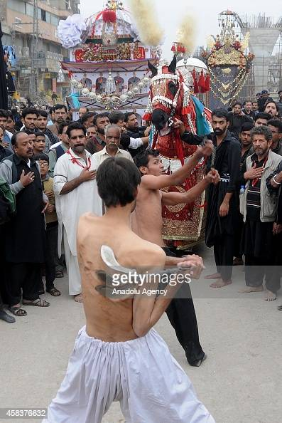Pakistani Shiite Muslim devotees flagellate themselves with knifefitted chains during the mourning procession of Ashura on the 10th day of holy month...