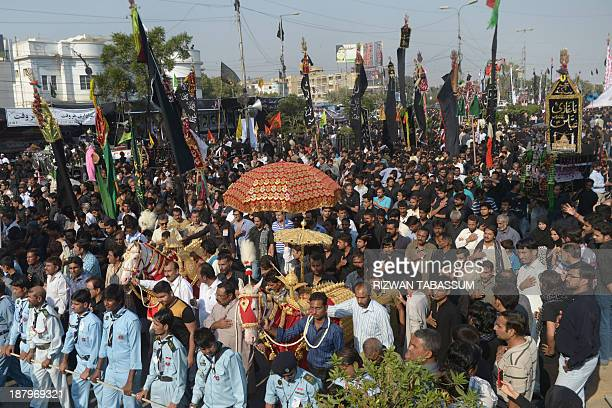 Pakistani Shiite Muslim devotees parade during a religious procession held ahead of Ashura on the ninth day of Muharram in Karachi on November 14...
