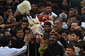 Pakistani Shiite Muslim devotees surround a symbolic horse during an Ashura procession to commemorate the martyrdom of Imam Hussain the grandson of...