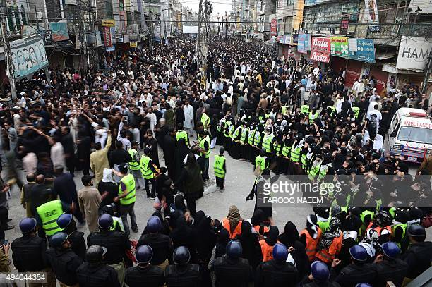 Pakistani Shiite Muslim devotees take part in an Ashura procession to commemorate the martyrdom of Imam Hussain the grandson of Prophet Muhammad in...