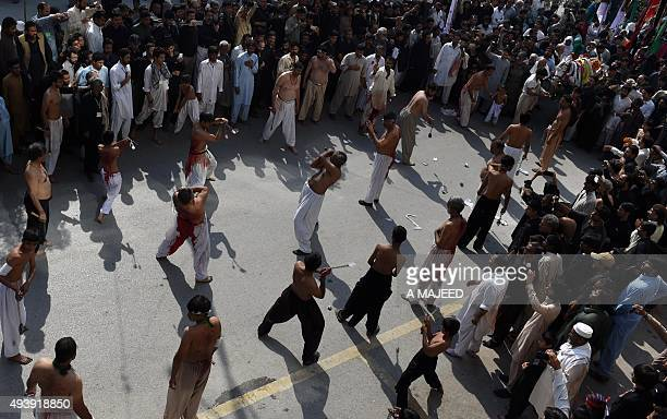 Pakistani Shiite Muslim devotees take part in ritual selfflagellation during an Ashura procession to commemorate the martyrdom of Imam Hussain the...