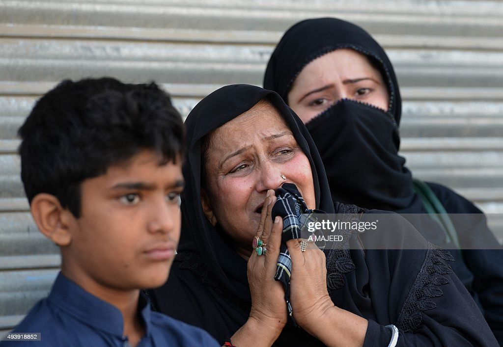 Pakistani Shiite Muslim devotees watch during an Ashura procession to commemorate the martyrdom of Imam Hussain the grandson of Prophet Muhammad in...