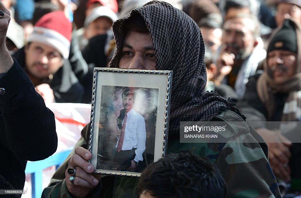 A Pakistani Shiite Muslim holds picture of bomb blast victim at a protest in Quetta on January 13, 2013, on the third day of protest. Pakistan's Prime Minister Raja Pervez Ashraf arrived, in the southwestern city of Quetta to meet Shiite Muslim families refusing to bury their dead after devastating bombings. AFP PHOTO/ Banaras KHAN