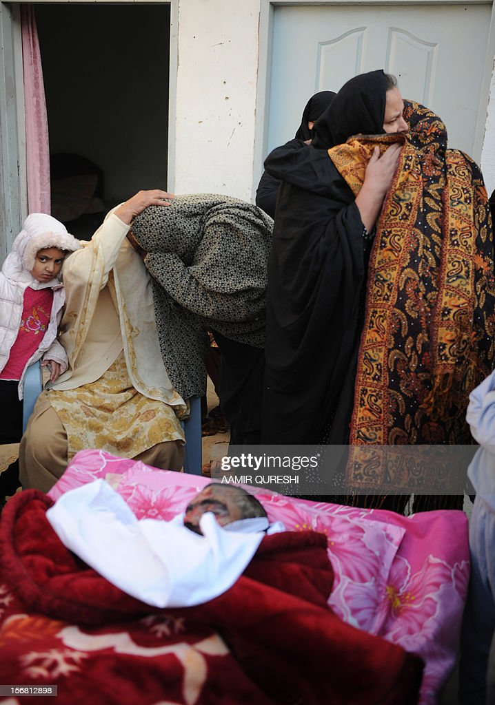 Pakistani Shiite Muslim mourn beside the body of a blast victim following an overnight suicide bomb attack on minority Shiite Muslims procession in Rawalpindi on November 22, 2012. A suicide bomber struck a night-time Shiite march in Pakistan, in the bloodiest attack of a day of violence that left at least 28 people dead as Islamic leaders gathered for a rare summit in Islamabad. Police in the garrison city of Rawalpindi near the capital said the attack on the procession of minority Shiite Muslims killed at least 16 people, after the suicide bomber blew himself up when he was stopped for a security check. AFP PHOTO/Aamir QURESHI