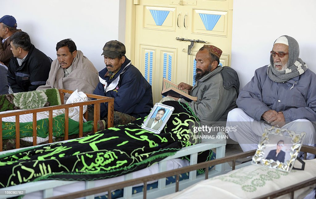 Pakistani Shiite Muslim mourners sit beside the coffins of blast victims at a mosque following overnight twin suicide bombings in Quetta on January 11, 2013. A string of bombings in Pakistan including a twin suicide attack on a snooker hall used by Shiite Muslims has left 114 people dead, in one of the deadliest days to hit the nation in years. AFP PHOTO / BANARAS KHAN