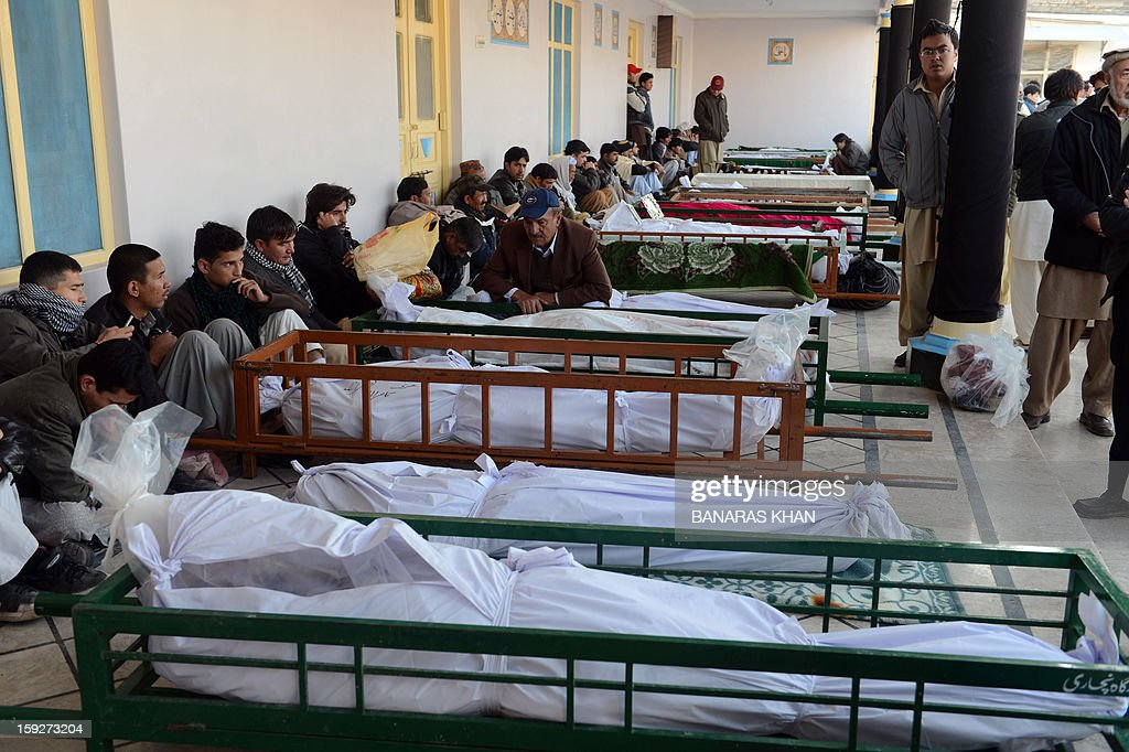Pakistani Shiite Muslim mourners sit beside the wrapped remains of blast victims at a mosque following overnight twin suicide bombings in Quetta on January 11, 2013. A string of bombings in Pakistan including a twin suicide attack on a snooker hall used by Shiite Muslims has left 114 people dead, in one of the deadliest days to hit the nation in years. AFP PHOTO / BANARAS KHAN