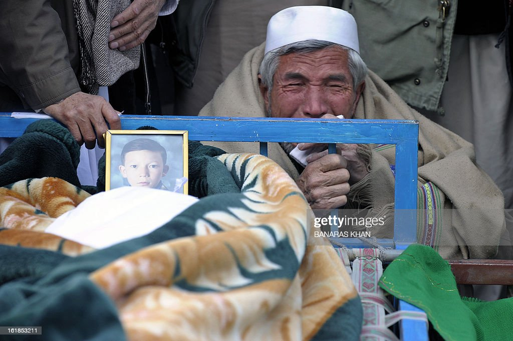 A Pakistani Shiite Muslim mourns in front of the coffin of his son as he gathers along with others during a protest against the killing of bomb attack victims in Quetta on February 17, 2013, a day after devastating bomb attack here. The death toll from a devastating bomb attack on Shiite Muslims in southwest Pakistan rose to 81 Sunday, as the community threatened protests if swift action was not taken against the killers. AFP PHOTO/Banaras KHAN