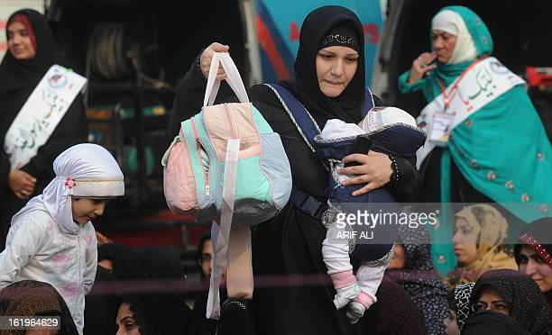 A Pakistani Shiite Muslim woman carries her child as she arrives to attend a protest against the bombing which killed 89 people in Quetta on February...