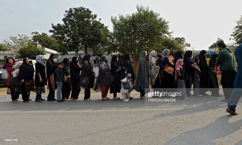 Pakistani Shiite Muslim women lineup for a security check during a religious procession on the ninth day of holy month of Moharram in Islamabad on November 24, 2012. The Pakistani Taliban have claimed responsibility for a bomb blast near a Shiite Muslim procession in northwest Pakistan that killed seven people. The blast went off as people from the minority Shiite Muslim community were gathering to mark the anniversary of the death of the Prophet Mohammed's grandson Imam Hussain in 680. AFP PHOTO/Farooq NAEEM