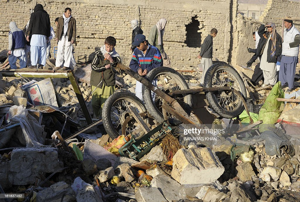 Pakistani Shiite Muslims are pictured amid debris at the scene of yesterday's bomb attack site in Quetta on February 17, 2013. The death toll from a devastating bomb attack on Shiite Muslims in southwest Pakistan rose to 81 Sunday, as the community threatened protests if swift action was not taken against the killers. AFP PHOTO/Banaras KHAN