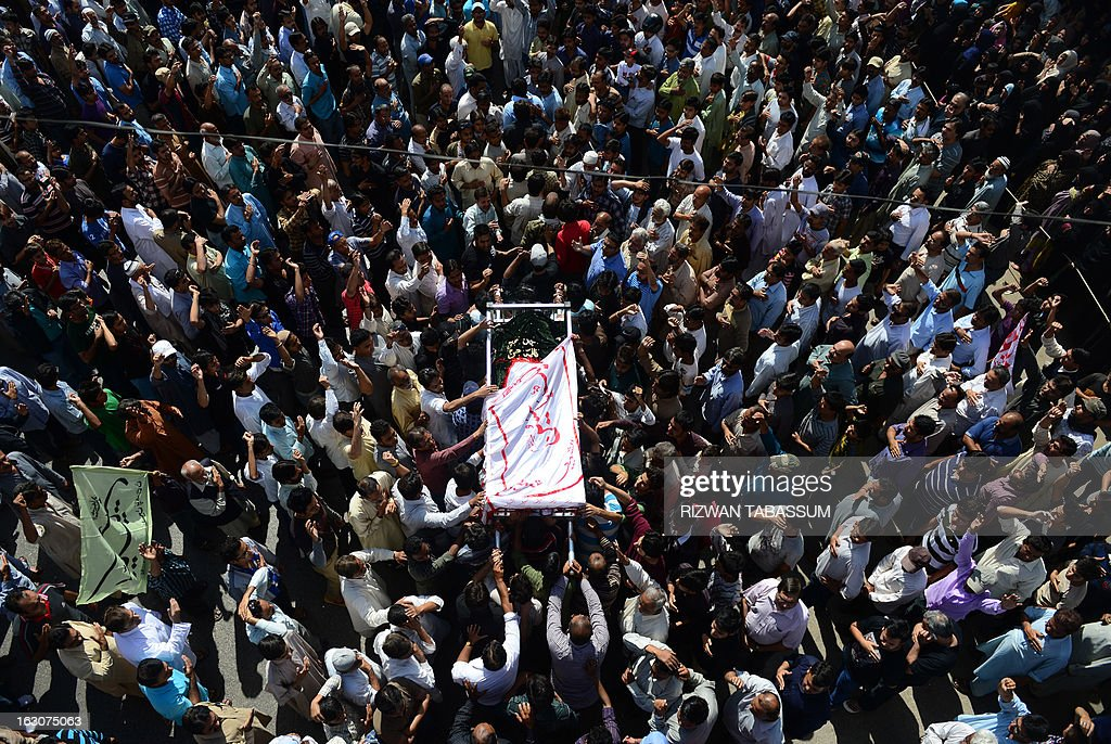 Pakistani Shiite Muslims carry a coffin during the funeral procession of bomb blast victims in Karachi on March 4, 2013. Thousands of Pakistanis attended funerals Monday for victims of a bombing that killed 48 people in a Shiite Muslim area of Karachi, the latest in a series of devastating attacks ahead of elections. AFP PHOTO/Rizwan TABASSUM