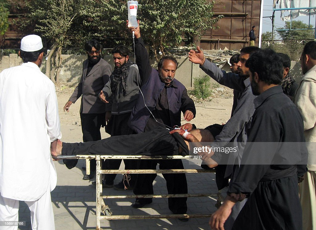 Pakistani Shiite Muslims carry an injured blast victim at a hospital following a bomb explosion in the city of Dera Ismail Khan in Khyber Pakhtunkhwa province on November 25, 2012. A bomb attack on a Shiite Muslim procession killed three people and wounded more than 50 in northwest Pakistan on November 25 as Shiites marked their holiest day Ashura, police said.