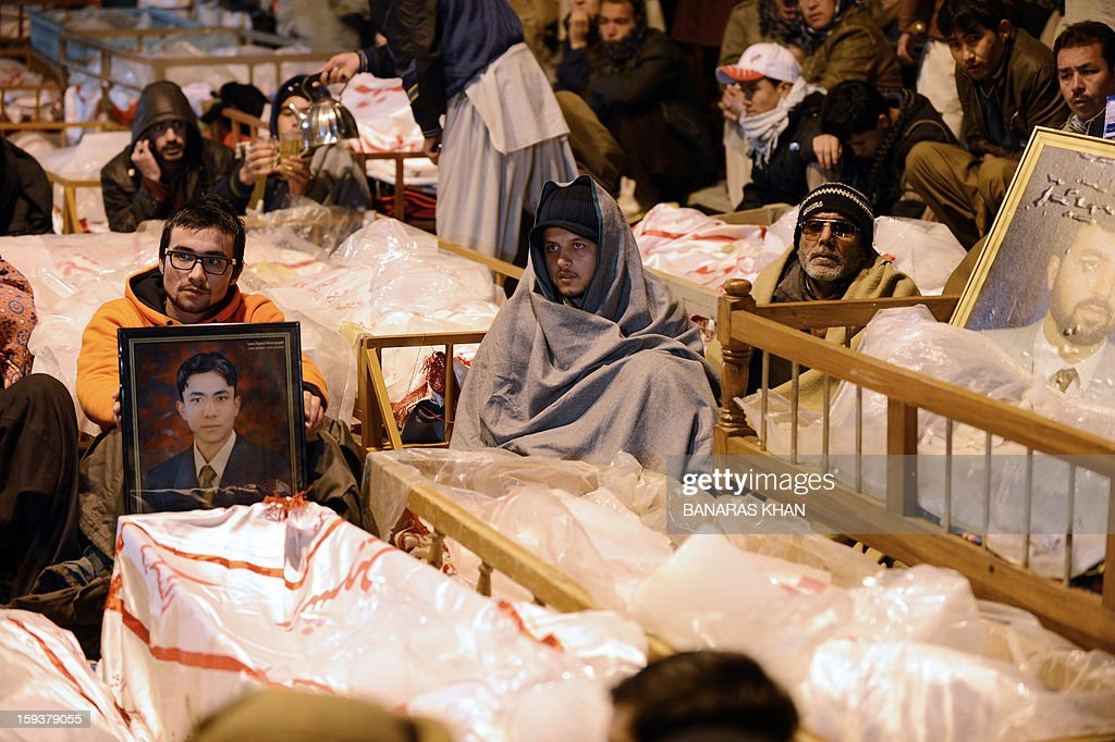 Pakistani Shiite Muslims demonstrate and sit amongst the coffins and portraits of bomb blast victims in Quetta on January 12, 2013. Shiite families refusing to bury their dead after twin bombings in Pakistan's troubled southwestern city of Quetta vowed to continue their sit-in protest until the army takes over security. Sunni militant group Lashkar-e-Jhangvi claimed responsibility for the bombings, which took place in an area dominated by Shiite Muslims from the Hazara ethnic minority and killed 92 people, with 121 wounded. AFP PHOTO / Banaras KHAN