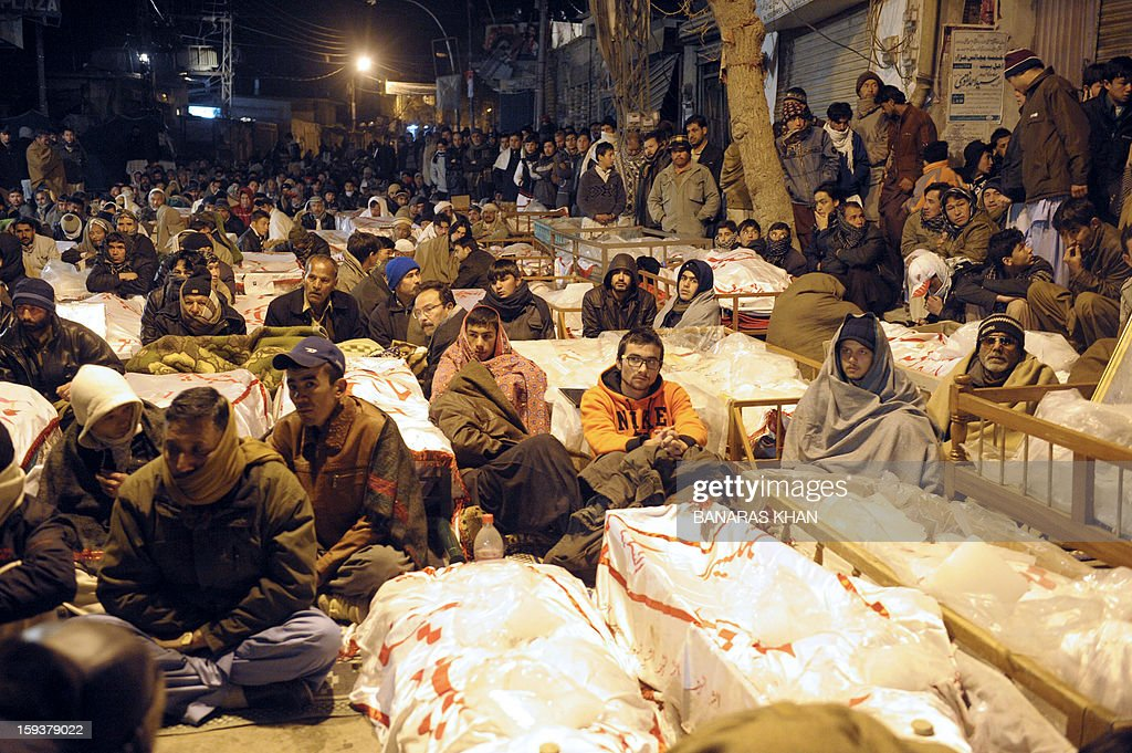 Pakistani Shiite Muslims demonstrate and sit between the coffins of bomb blast victims in Quetta on January 12, 2013. Shiite families refusing to bury their dead after twin bombings in Pakistan's troubled southwestern city of Quetta vowed to continue their sit-in protest until the army takes over security. Sunni militant group Lashkar-e-Jhangvi claimed responsibility for the bombings, which took place in an area dominated by Shiite Muslims from the Hazara ethnic minority and killed 92 people, with 121 wounded. AFP PHOTO / Banaras KHAN