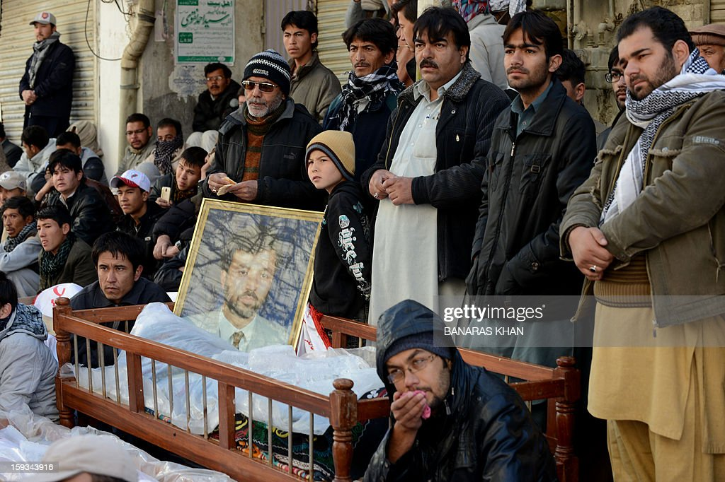 Pakistani Shiite Muslims demonstrate as they sit between the coffins of bombing victims in Quetta on January 12, 2013. Shiite families refusing to bury their dead after twin bombings in Pakistan's troubled southwestern city of Quetta vowed to continue their sit-in protest January 12 until the army takes over security. AFP PHOTO/Banaras KHAN