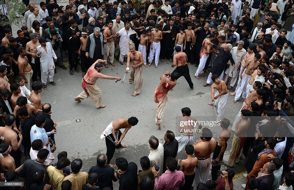 Pakistani Shiite Muslims flagellate themselves during a religious procession on the ninth day of holy Islamic month of Moharram in Peshawar on...