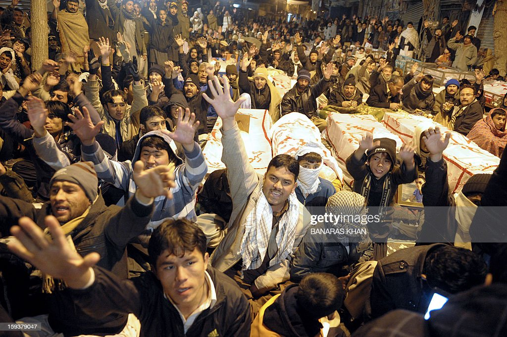 Pakistani Shiite Muslims gesture as they demonstrate and sit between the coffins of bomb blast victims in Quetta on January 12, 2013. Shiite families refusing to bury their dead after twin bombings in Pakistan's troubled southwestern city of Quetta vowed to continue their sit-in protest until the army takes over security. Sunni militant group Lashkar-e-Jhangvi claimed responsibility for the bombings, which took place in an area dominated by Shiite Muslims from the Hazara ethnic minority and killed 92 people, with 121 wounded. AFP PHOTO / Banaras KHAN
