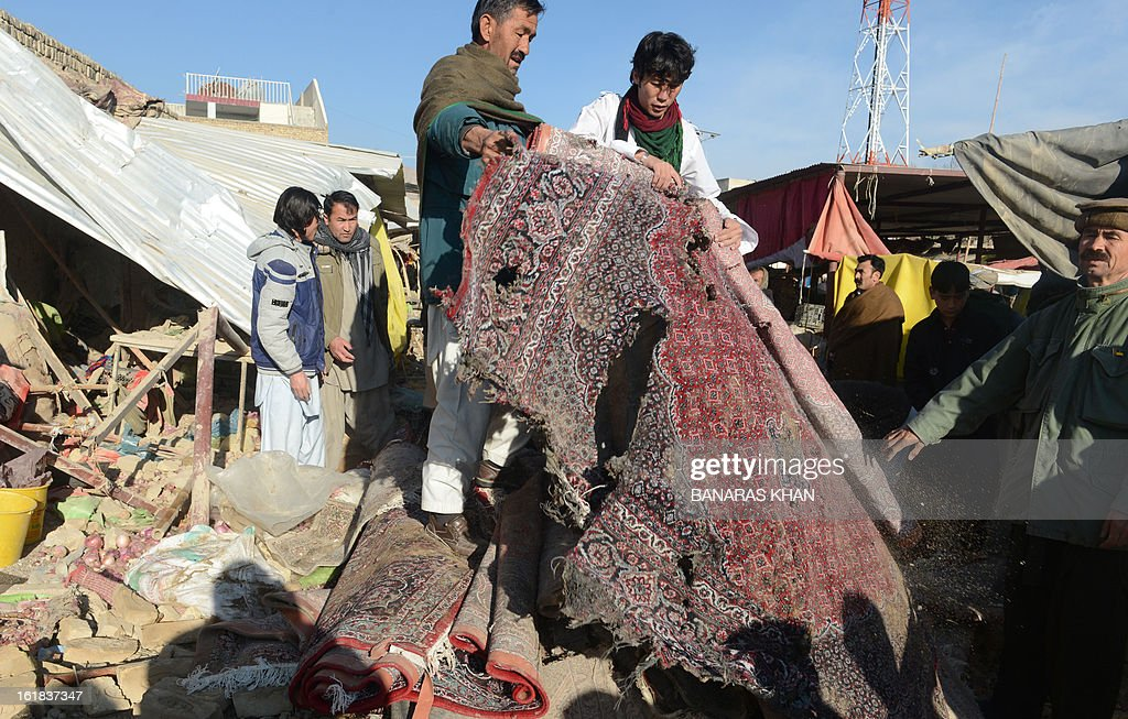 Pakistani Shiite Muslims hold up a shredded carpet amid debris at the scene of yesterday's bomb attack site in Quetta on February 17, 2013. The death toll from a devastating bomb attack on Shiite Muslims in southwest Pakistan rose to 81 Sunday, as the community threatened protests if swift action was not taken against the killers. AFP PHOTO/Banaras KHAN
