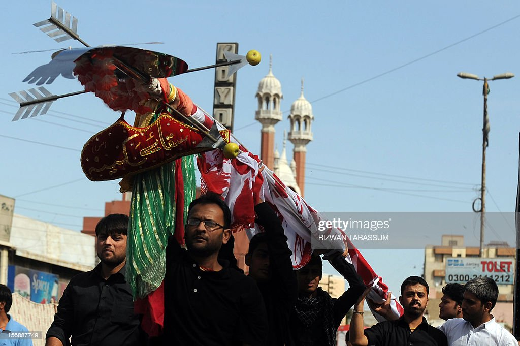 Pakistani Shiite Muslims march during a religious procession on the ninth day of holy month of Moharram in Karachi on November 24, 2012. A bomb exploded near a Shiite religious procession in northwest Pakistan on November 24 killing seven people including four children, hospital officials said. It commemorates the death of Imam Hussain, the grandson of the Prophet Mohammed, along with his close relatives and supporters in the Battle of Karbala in modern-day Iraq in the year 680. AFPPHOTO/Rizwan TABASSUM