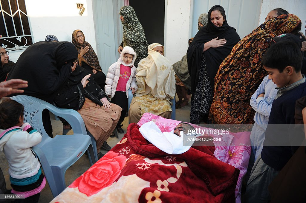Pakistani Shiite Muslims mourn beside the body of a blast victim following an overnight suicide bomb attack on minority Shiite Muslims procession in Rawalpindi on November 22, 2012. A suicide bomber struck a night-time Shiite march in Pakistan, in the bloodiest attack of a day of violence that left at least 28 people dead as Islamic leaders gathered for a rare summit in Islamabad. Police in the garrison city of Rawalpindi near the capital said the attack on the procession of minority Shiite Muslims killed at least 16 people, after the suicide bomber blew himself up when he was stopped for a security check. AFP PHOTO/Aamir QURESHI