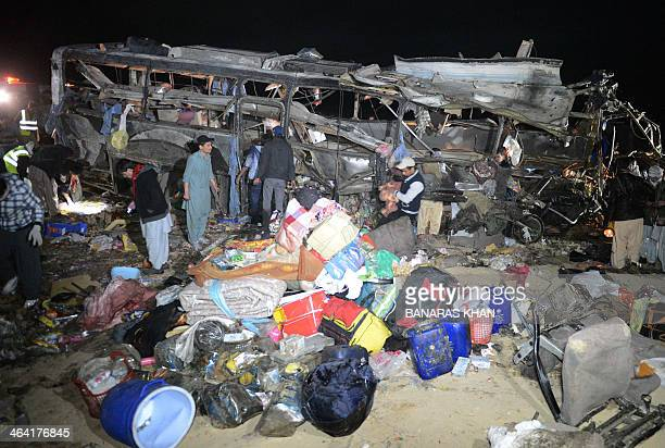 Pakistani Shiite Muslims search a destroyed pilgrims bus after a bomb attack at Dringhar village on the PakistanIran highway some 60 kilometres west...