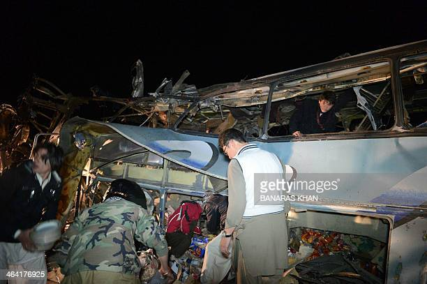 Pakistani Shiite Muslims search wreckage of a destroyed pilgrims bus after a bomb attack at Dringhar village on the PakistanIran highway some 60...