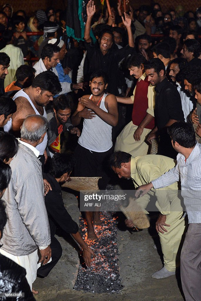 Pakistani Shiite Muslims walk on burning coal during a procession in Lahore late November 22, 2012, in the Muslim holy month of Muharram - as devotees remember the slaying of the Prophet Mohammed's grandson in southern Iraq in the seventh century. During the Shiite Muslim holy month of Muharram, large processions are formed and the devotees parade the streets holding banners and carrying models of the mausoleum of Hazrat Imam Hussain and his people, who fell at Karbala. Shias show their grief and sorrow by inflicting wounds on their own bodies with sharp metal tied to chains to depict the sufferings of the martyrs. AFP PHOTO/Arif ALI