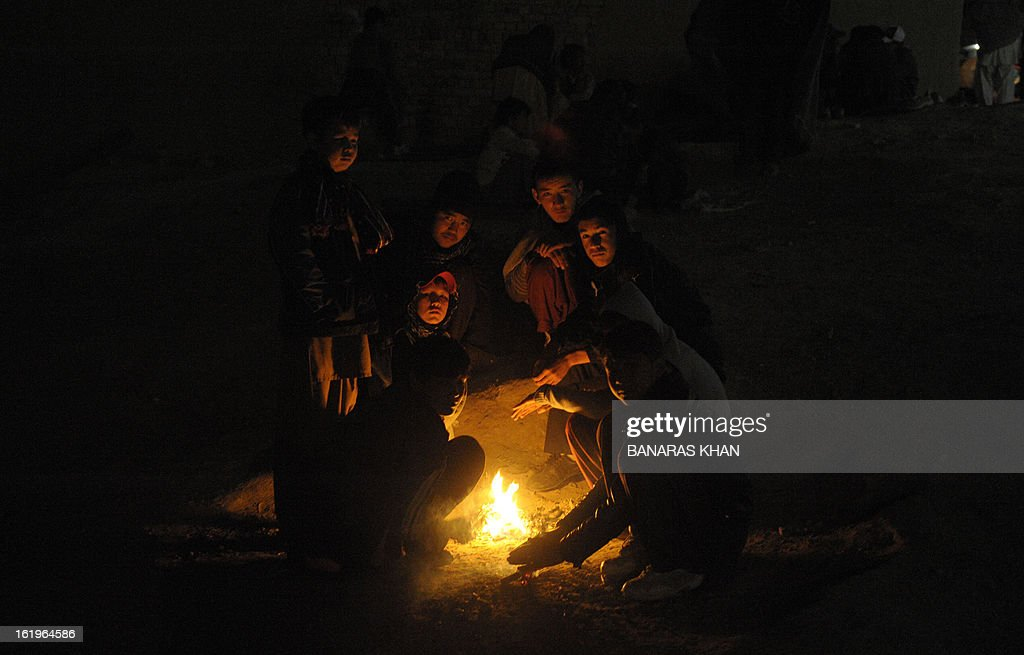 Pakistani Shiite Muslims warm themselves around a fire as they gather to protest against the bombing which killed 89 people, in Quetta on February 18, 2013. Thousands of Pakistani Shiites refused for a second day Monday to bury victims of a devastating bomb attack on their community, demanding protection against record levels of sectarian violence. AFP PHOTO/ Banaras KHAN