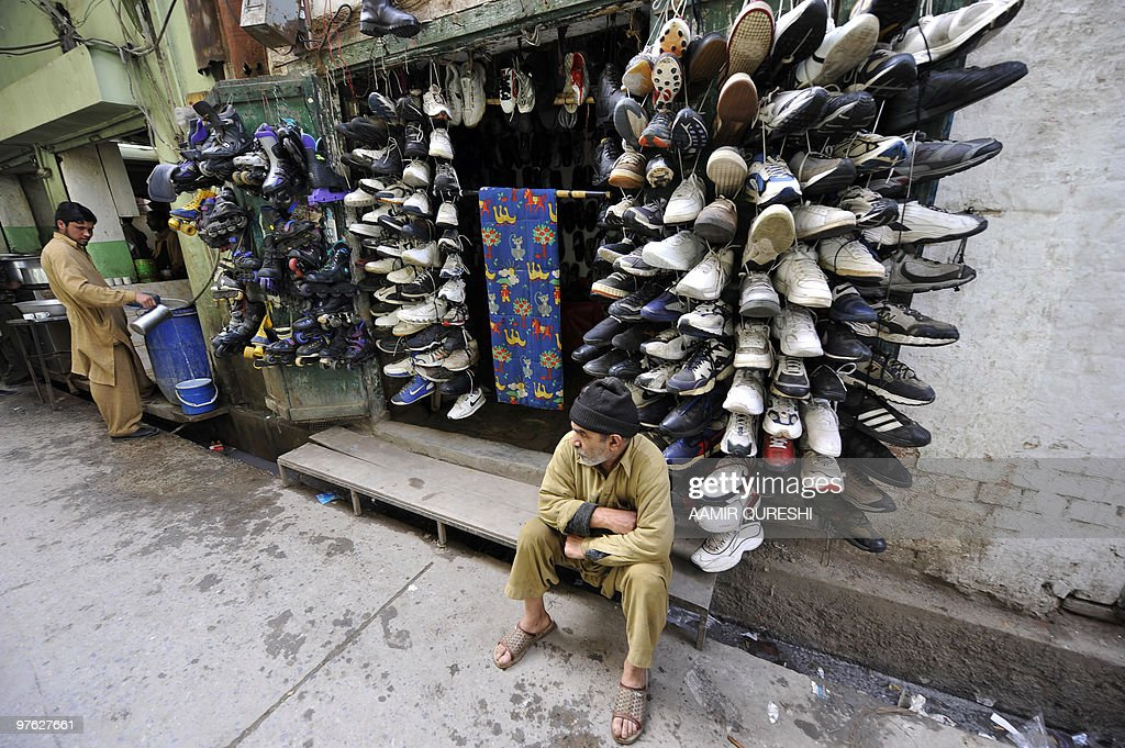 A Pakistani shoe vendor waits for customers at a market in Rawalpindi on March 4 2010 AFP PHOTO/ AAMIR QURESHI