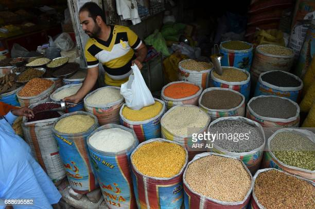 A Pakistani shopkeeper sells pulses at a market in Lahore on May 26 2017 Pakistan's economy expanded almost 53 percent in the last year the country's...