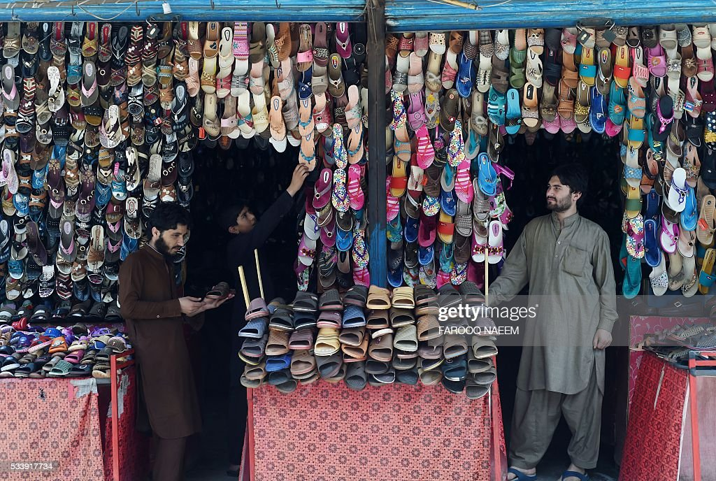 Pakistani shopkeepers wait for customers at a shoe stall at a market in Rawalpindi on May 24, 2016. / AFP / FAROOQ