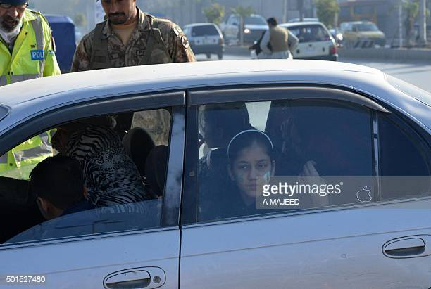 A Pakistani soldier conducts a security check of a family on their way to attend a ceremony to mark the first anniversary of the school massacre...