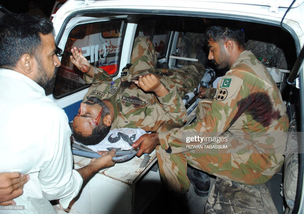 A Pakistani soldier sits next to his wounded colleague as they arrive at a hospital following a roadside bomb explosion in Karachi on August 22, 2013. A roadside bomb killed a man and wounded at least 16 people on August 22 including soldiers and civilians in Pakistan's violence-plagued port city of Karachi, police said. The bomb targeted troops returning to camp by truck after carrying out security duties for by-elections in the city.