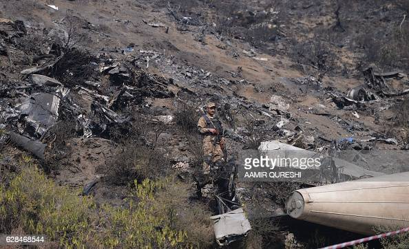 A Pakistani soldier stands beside the wreckage of the crashed PIA passenger plane Flight PK661 near the village of Saddha Batolni in the Abbottabad...