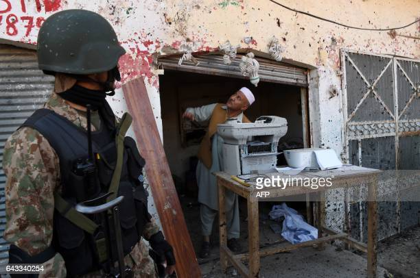 Pakistani soldier stands guard as a shopkeeper examines damage at the site of a court complex after multiple Taliban suicide bomb attacks in the...