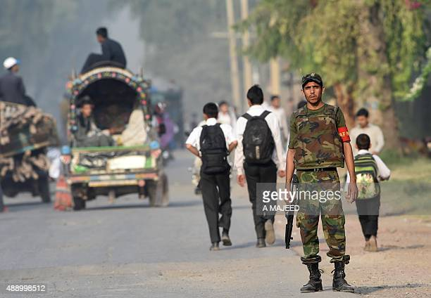 A Pakistani soldier stands guard outside an Air Force base a day after it was attacked by militants in Peshawar on September 19 2015 Pakistani...