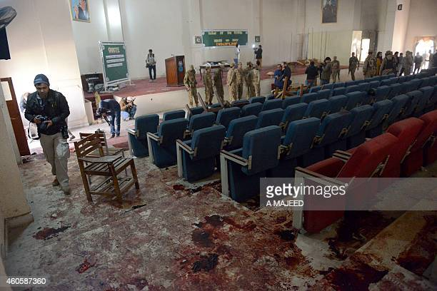 Pakistani soldiers and media gather in a ceremony hall at an armyrun school a day after an attack by Taliban militants in Peshawar on December 17...