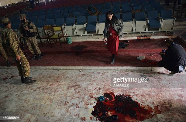 Pakistani soldiers and media stand inside an assembly hall at an armyrun school following an attack there by militants in Peshawar on December 17...