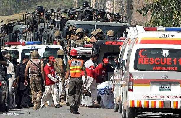 Pakistani soldiers arrive to take position as volunteers move an injured person outside a Pakistan Air Force base after an attack by militants in...