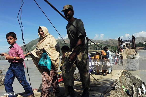 Pakistani soldiers assist flood affected families as they cross over a damaged bridge at Chakdarra in Swat on August 4 2010 The international...