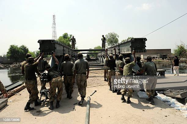 Pakistani soldiers build a temporary bridge in the flooded area of Kasbag Gujarat some 60 km west of Multan on August 21 2010 United Nations agencies...