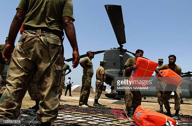Pakistani soldiers carry food parcels brought by United Arab Emirates helicopters in the Tunsa area of southern Punjab on August 18 2010 Foreign aid...