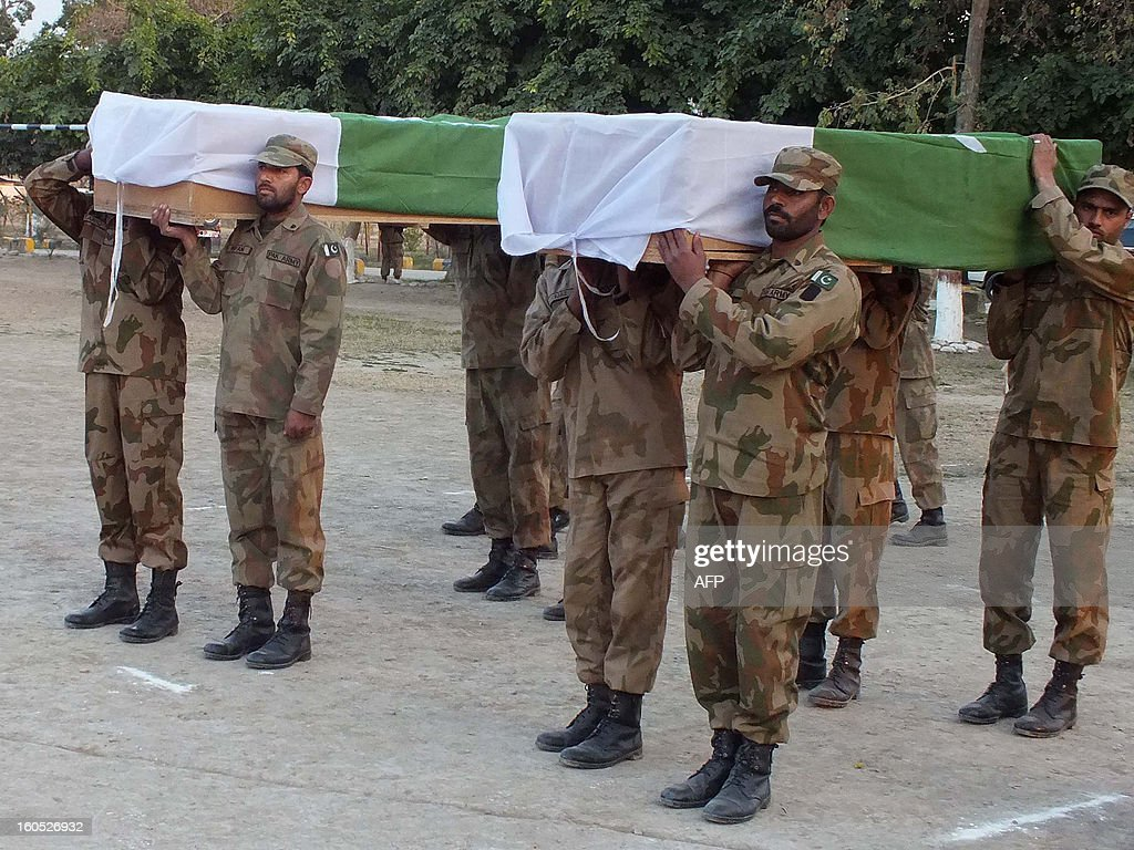 Pakistani soldiers carry the coffins of their fallen comrades killed in a suicide attack, during a funeral in Sari Norang on February 2, 2013. Suicide bombers attacked a military checkpost in Pakistan's troubled northwest on Saturday, killing 13 soldiers and 11 civilians, officials said, in an assault claimed by the Taliban. AFP PHOTO/Karim ULLAH
