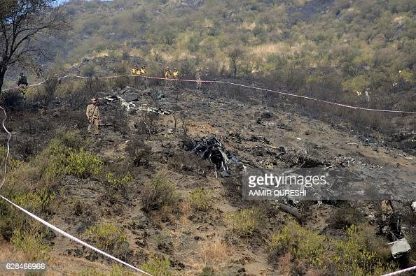 Pakistani soldiers cordon off a plane crash site in the village of Saddha Batolni in the Abbottabad district of Khyber Pakhtunkhwa province on...